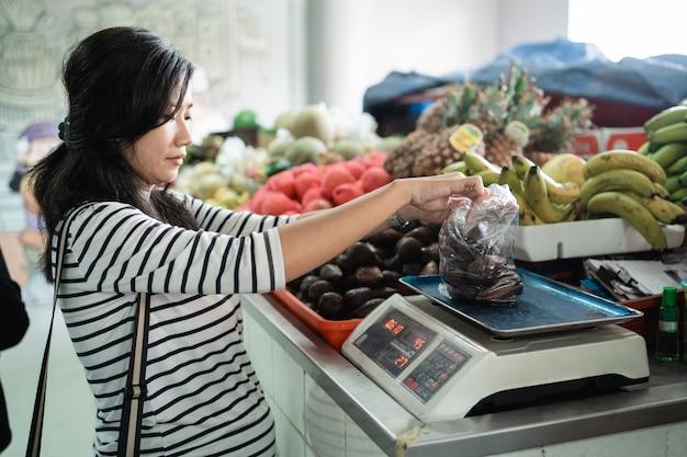 Mujer asiática embarazada pesa los artículos comprados