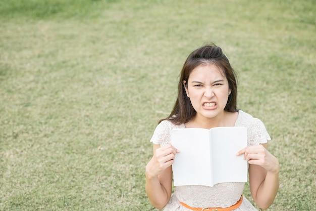 Mujer asiática con la emoción de la tensión con un libro a disposición en fondo borroso del piso de la hierba