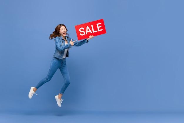 Mujer asiática emocionada saltando con cartel de venta rojo