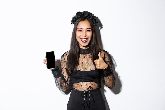 Mujer asiática emocionada y satisfecha en disfraz de halloween que muestra el pulgar hacia arriba en señal de aprobación y demuestra la pantalla del teléfono móvil, de pie sobre una pared blanca