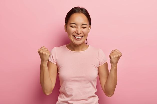 La mujer asiática emocional exitosa aprieta los puños en el aire, celebra el éxito, tiene una amplia sonrisa, mantiene los ojos cerrados, está emocionada y alegre, disfruta del dulce sabor de la victoria, usa ropa informal.