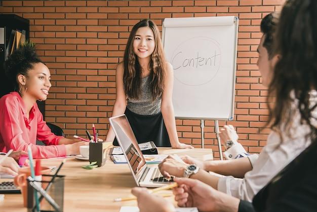 Mujer asiática empresaria líder en la reunión con sus colegas multiétnicos