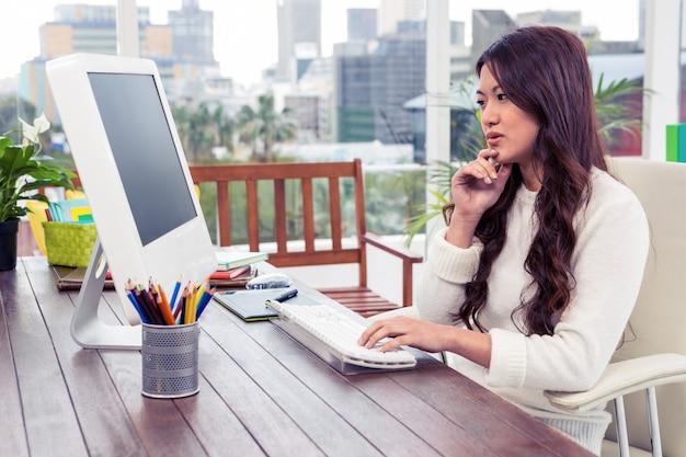 Mujer asiática enfocada que usa la computadora con la mano en la barbilla en oficina