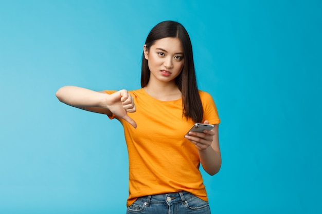 Mujer asiática enojada corte de pelo oscuro corto frunciendo el ceño haciendo muecas decepcionado mostrar pulgar hacia abajo desaprobar ...