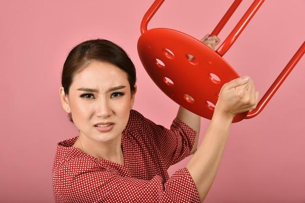 Mujer asiática enojada, mujer gritando con furioso gesto agresivo de la mano en la pared rosada, expresión de la cara y emoción humana.