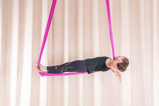 Mujer asiática de entrenamiento en sala de fitness con elementos de yoga volar