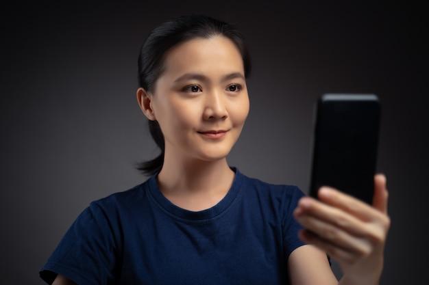 Mujer asiática escanea la cara por teléfono inteligente con sistema de reconocimiento facial. aislado en el fondo.