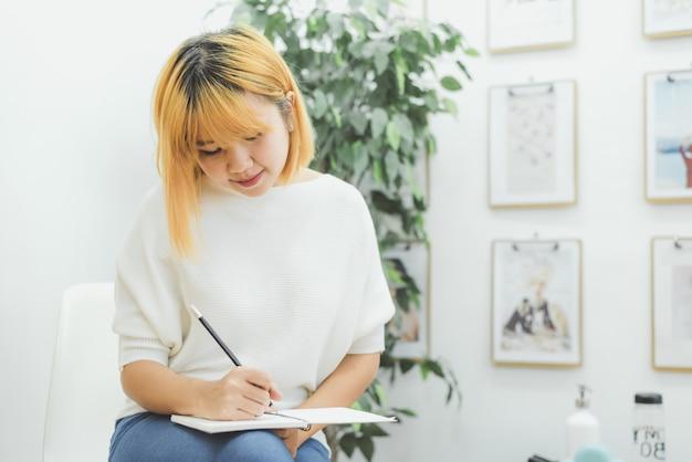 La mujer asiática escribe listas de compras en la libreta por la pluma en su contador de la cocina en casa y leyendo