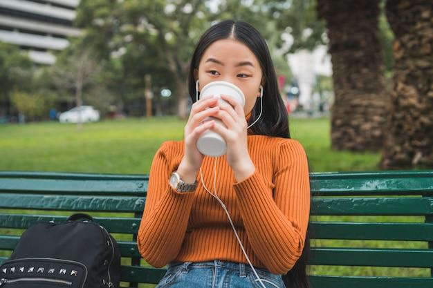 Mujer asiática escuchando música y tomando café.