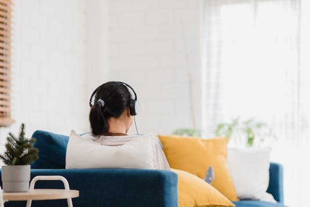 Mujer asiática escuchando música y usando mesa