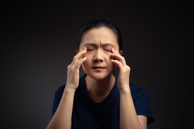La mujer asiática estaba enferma con dolor en los ojos, irritaba y picaba los ojos, aislado en el fondo.