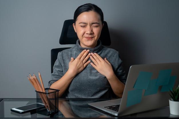 Mujer asiática estaba enferma de fiebre, trabajando en una computadora portátil en la oficina