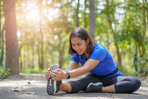 Mujer asiática estirar los músculos en el parque y escuchar música