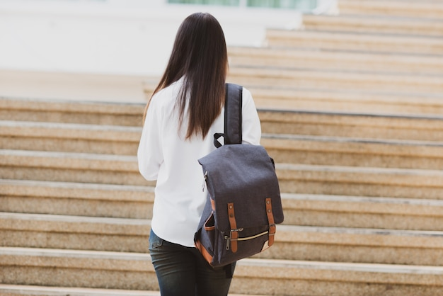 Mujer asiática del estudiante con el ordenador portátil y el bolso, concepto de la educación