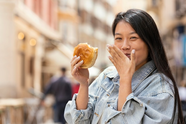 Mujer asiática feliz después de comprar comida en la calle