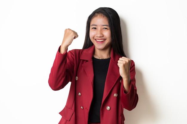 Mujer asiática feliz y emocionada celebrando la victoria expresando energía de gran éxito y emociones positivas.