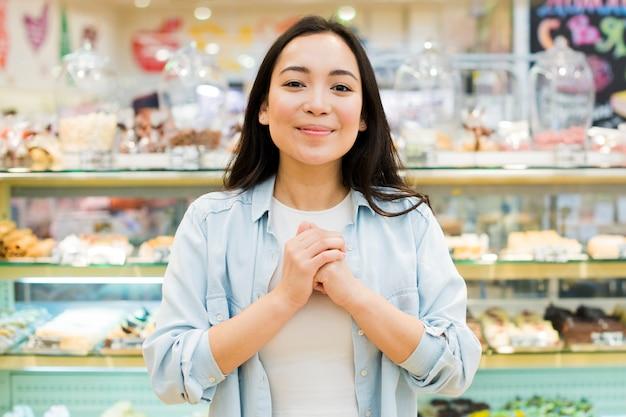 Mujer asiática feliz que se coloca con las manos en pecho en tienda de pasteles