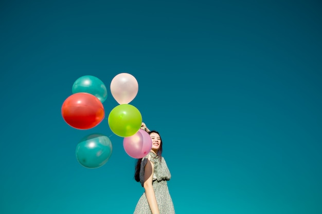 Mujer asiática feliz que juega los globos coloridos en el cielo azul. concepto de libertad