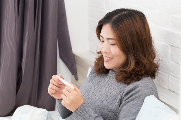 Mujer asiática feliz que lleva a cabo la prueba de embarazo y que se acuesta en la cama