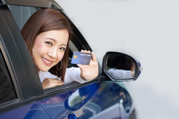 La mujer asiática feliz que sostiene la tarjeta de crédito muestra la tarjeta y sonríe en el coche.