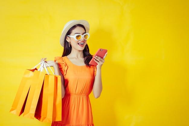Mujer asiática feliz que usa el teléfono celular en el fondo amarillo, estación del otoño