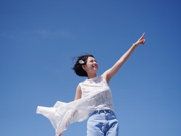 Mujer asiática feliz y sonrisa en la playa y el cielo azul