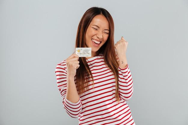 La mujer asiática feliz en suéter se regocija y que sostiene la tarjeta de crédito sobre fondo gris