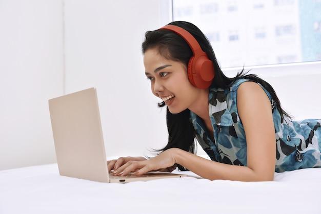 Mujer asiática feliz usando laptop y disfrutando de la música