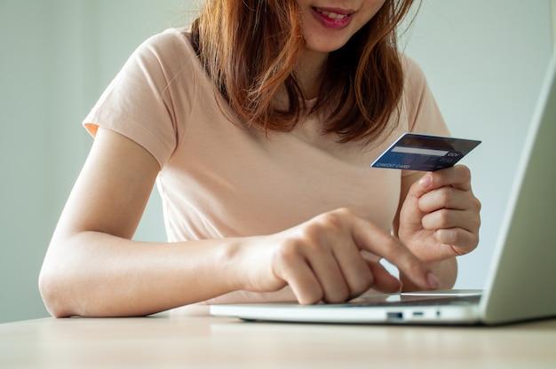 Una mujer asiática está feliz de usar tarjetas de crédito para comprar en línea
