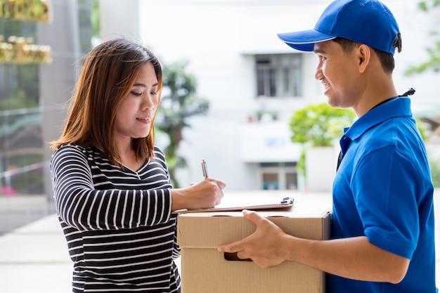 Mujer asiática firma el recibo del paquete entregado