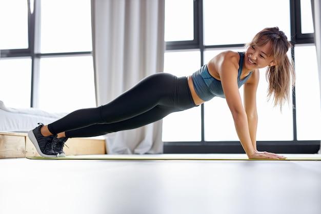 Mujer asiática fitness haciendo push up, hermosa mujer en entrenamiento de ropa deportiva sola