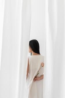 Mujer asiática con una flor de peonía rosa seca en una mano entre la cortina blanca