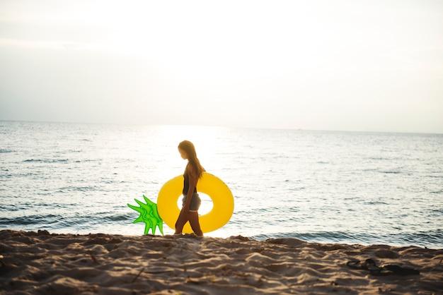 Una mujer asiática con flotador inflable en la playa.