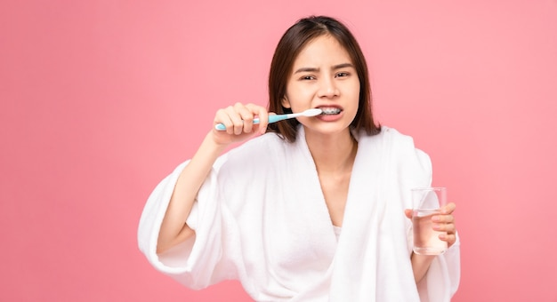 Mujer asiática con frenillos con cepillado de dientes y sosteniendo un vaso de agua, toalla en el hombro sobre fondo rosa, concepto de higiene bucal y cuidado de la salud