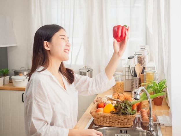 Mujer asiática con fruta en la cocina.