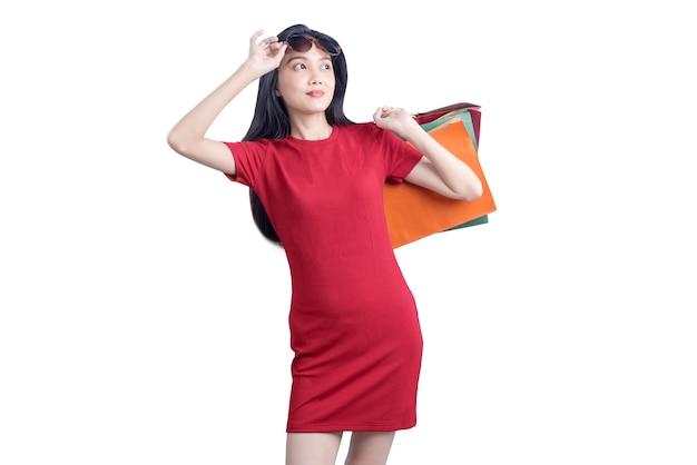 Mujer asiática con gafas de sol llevando bolsas de la compra aislado sobre fondo blanco.