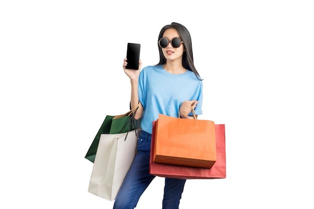 Mujer asiática con gafas de sol llevando bolsas de la compra con teléfono móvil aislado sobre fondo blanco.