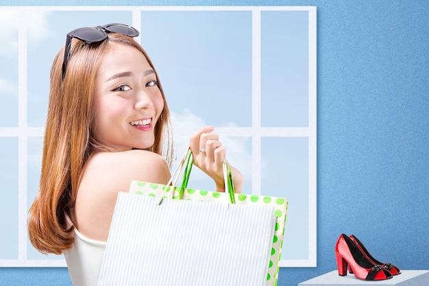 Mujer asiática, con, gafas de sol, proceso de llevar, bolsas de compras, posición, con, pared azul
