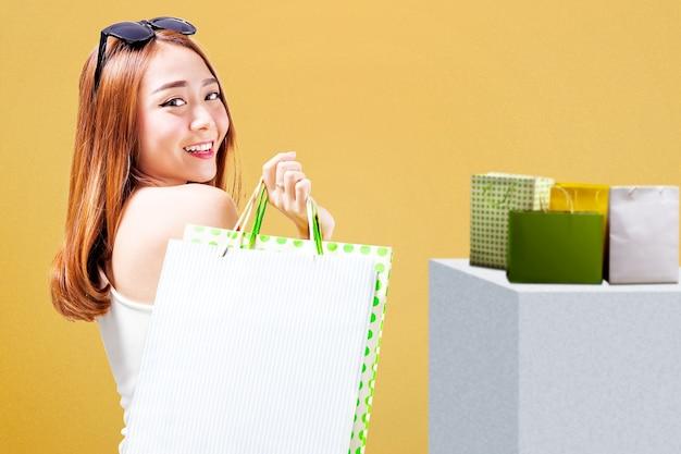 Mujer asiática, con, gafas de sol, proceso de llevar, bolsas de compras, posición