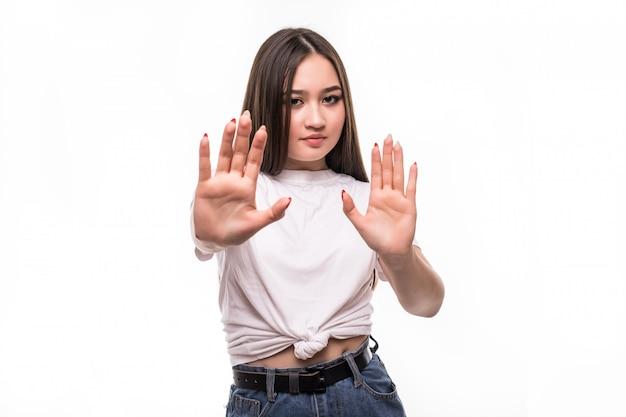 Mujer asiática con un gesto de parada aislado en la pared blanca