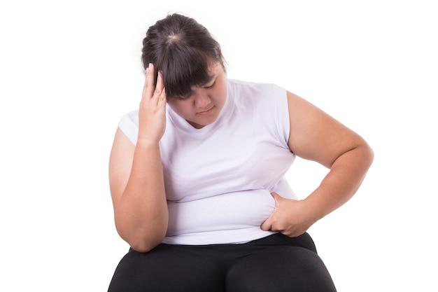 La mujer asiática gorda usa la camiseta blanca preocupada por su tamaño del cuerpo