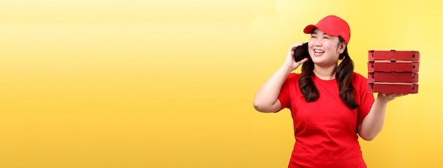 Mujer asiática en gorra roja, dando orden de alimentos pizza italiana en cajas de cartón aisladas con teléfono móvil.