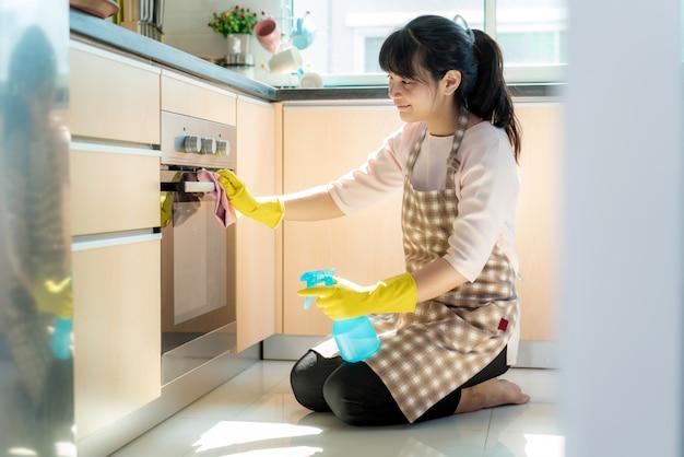 Mujer asiática con guantes protectores de goma que limpian el horno en su hogar durante su estadía en casa utilizando el tiempo libre sobre su rutina diaria de limpieza.