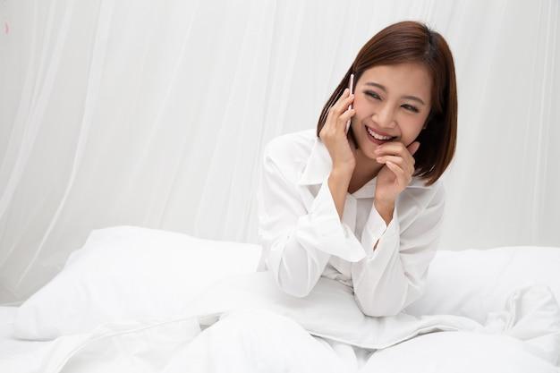 Mujer asiática hablando por teléfono en la cama blanca.