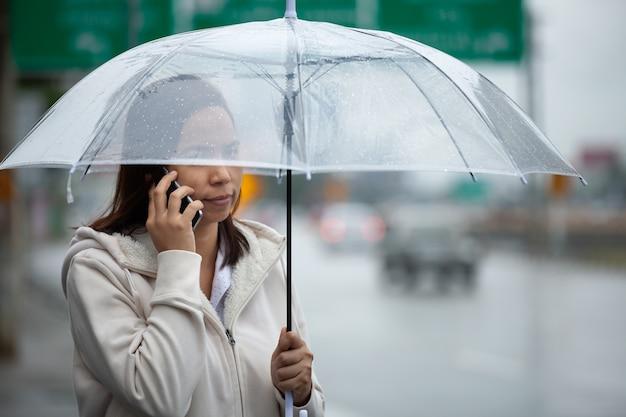 Mujer asiática hablando por un teléfono celular y sosteniendo un paraguas mientras está de pie en la calle de la ciudad en el día lluvioso.