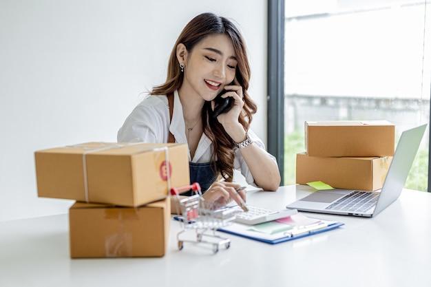 Una mujer asiática está hablando por teléfono con un cliente para confirmar un pedido, es dueña de una tienda en línea, empaca y envía a través de una empresa de transporte privada. conceptos de venta online y compra online.