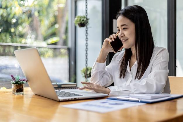 Mujer asiática hablando por teléfono, es vendedora en una empresa de nueva creación, llama a los clientes para vender productos y promociones. concepto de venta de productos a través de canales telefónicos.