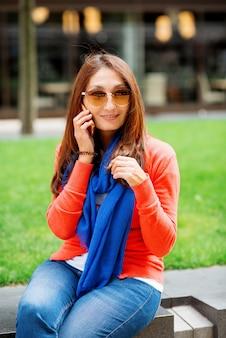 Mujer asiática hablando por teléfono móvil y sentado en el centro de la ciudad inglesa