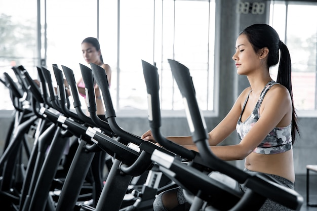 Mujer asiática está haciendo ejercicio con el cardio en el gimnasio.