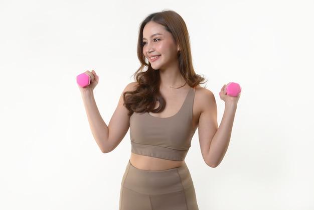 Mujer asiática haciendo ejercicio con pesas para una buena salud en blanco